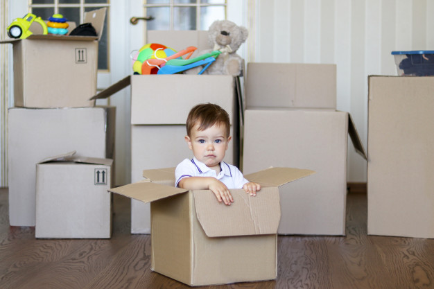 Bébé assis dans un carton lors du déménagement.